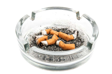 Glass ashtray with five cigarette buds on white background