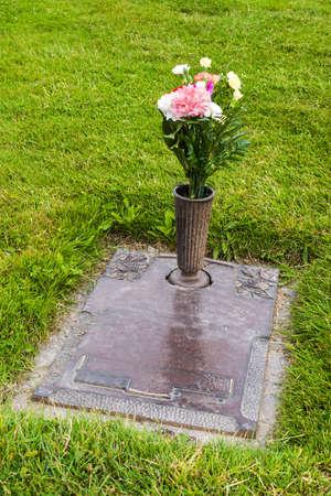 묘지 잔디에 꽃병에 꽃과 함께 무덤