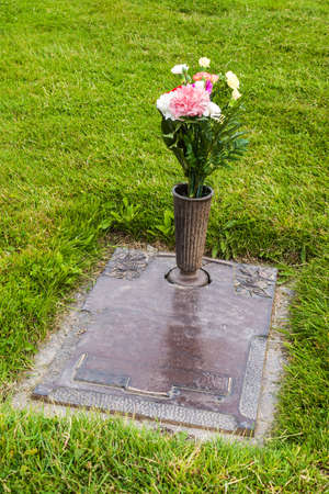 Grave with flowers in the vase, on the grass, at the graveyard