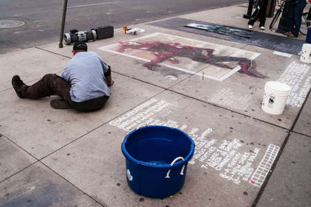 conceived: Street artist painting the pavement on Yonge Dundas Square in Toronto. The square was conceived in 1998 and was designed by Brown and Storey Architects.
