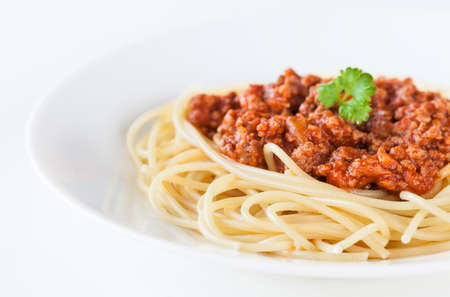 Spaghetti bolognese decorated with coriander leaf on a white plate and on white background