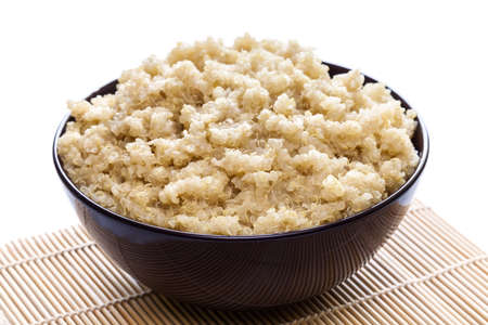 Cooked organic quinoa in brown bowl on white background Stock Photo