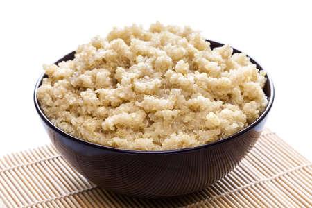 Gekookte organische quinoa in bruin kom op witte achtergrond
