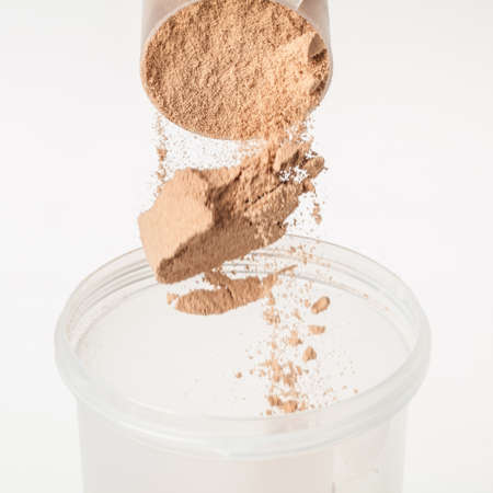 Scoop of chocolate whey isolate protein tossed into plastic white shaker, with focus on the protein in the scoop and falling protein blurred Stock Photo