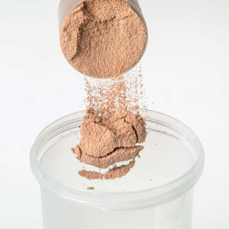 whey: Scoop of chocolate whey isolate protein tossed into plastic white shaker, with focus on the protein in the scoop and falling protein blurred Stock Photo