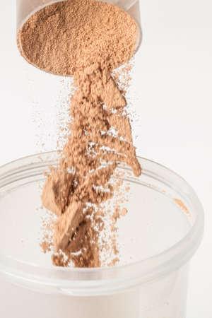 Bolletje chocolade wei-isolaat eiwit gegooid in witte plastic shaker, met focus op het eiwit in de primeur en dalende eiwit wazig