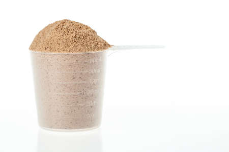 Plastic scoop of chocolate whey isolate protein on white background