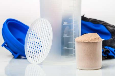 Scoop van wei-eiwit in de voorkant van fitnessapparatuur: handdoek, handschoenen en een shaker Stockfoto