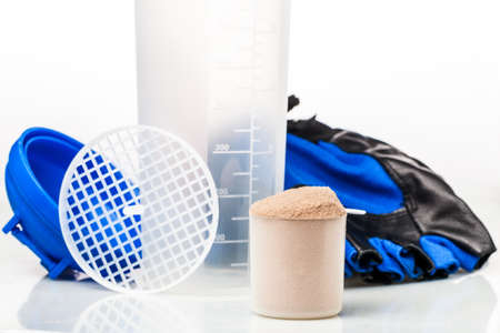 Scoop of whey protein in front of gym equipment: gloves and shaker parts photo