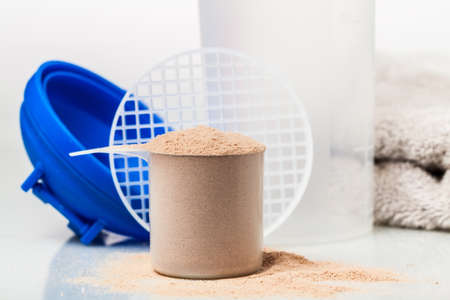 Scoop of whey protein in front of gym equipment: towel, gloves and shaker