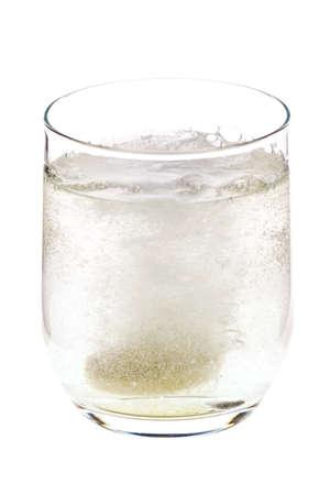 Fizzing pil gegooid in het glas, het oplossen en het vrijgeven van bubbels, geïsoleerd op een witte achtergrond Stockfoto