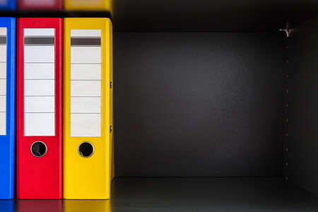 dossier: Red, green, blue and yellow office folders with boxes on the gray shelf