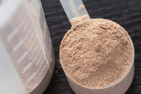 Scope of chocolate whey isolate protein next to the translucent protein shaker Foto de archivo