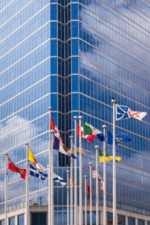 Flags of Canada and Canadian provinces against the Waterfront Centre building at 200 Burrard Street in downtown Vancouver  Building was completed in 1991 and rises 22 storeys  92 m  high
