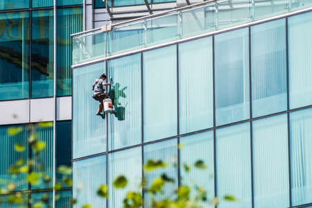 Man washing windows on a glass skyscraper in Vancouver downtown