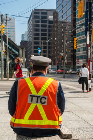 king street: TORONTO, CANADA - MAY 10, 2007: Officer of  Toronto Transit Commission observing traffic in downtown, at University Avenue and King Street West. TTC is public transport agency that operates transit bus and streetcar services in Toronto.
