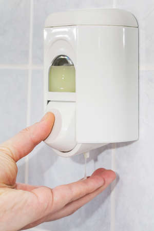 Hand of a man taking soap from the dispenser