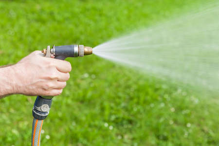 Man s hand holding water sprinkler while gardening, water spraying out of sprinkler on the grass
