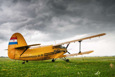 clouded: ZAGREB, CROATIA - JULY 18, 2008: Air Tractor Antonov AN-2 parked on a grass airfield Lucko under a heavily clouded sky, just before a storm broke. An-2  is Soviet mass-produced single-engine biplane utilityagricultural aircraft.