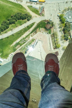 TORONTO, CANADA - MAY 7, 2007: Mans feet on the glass floor of the CN tower, 350 meters above ground level.  Glass Floor has been specifically designed for visitors fun and they can walk or crawl across it, sit on it or even jump on it.