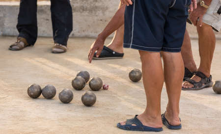 Group of senior citizens playing game of boules (petanque, bocce) on the playing field. Boules is a popular recreational activity of senior citizens in Dalmatia region of Croatia.
