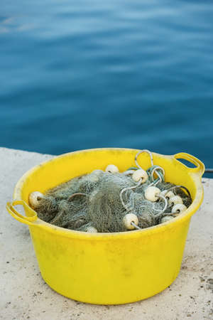 fishermans net: Gray fishing net on the heap in the yellow plastic container, with blue sea in the background