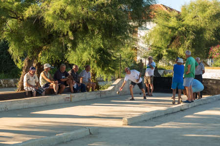 VELI IZ, CROATIA - AUGUST 23, 2014: Group of senior citizens playing game of boules (petanque, bocce) on the playing field. Boules is a popular recreational activity of senior citizens in Dalmatia region of Croatia. Editorial