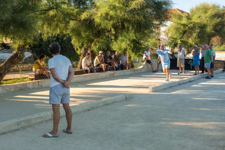boules: VELI IZ, CROATIA - AUGUST 23, 2014: Group of senior citizens playing game of boules (petanque, bocce) on the playing field. Boules is a popular recreational activity of senior citizens in Dalmatia region of Croatia. Editorial