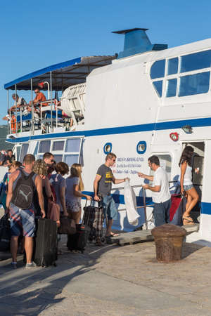VELI IZ, CROATIA - AUGUST 21, 2014: Passengers on main pier boarding the Jadrolinija boat in city of Veli Iz on the island Iz in Adriatic Sea. Editorial