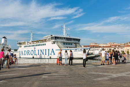 ZADAR, CROATIA - AUGUST 21, 2014: Passengers waiting for the arrival of Jadrolinija car ferry to Zadar old city port. Jadrolinija is state-owned with main mission in connecting Croatian islands to the mainland.