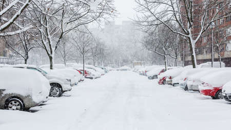 Cars covered in snow on a parking lot in the residential area during December snowfall