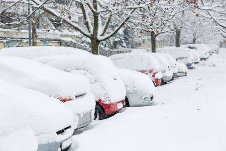 Auto's bedekt met sneeuw op een parkeerplaats in de woonwijk in december sneeuwval