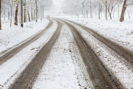 drivers: Traces of car tires on the street during heavy snowstorm, tracks visible and the road still not cleaned, presenting danger for drivers -  accident waiting to happen