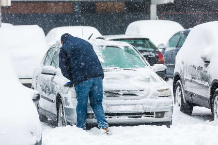 Man scraping frozen snow from the car windows during the heavy snowfall photo