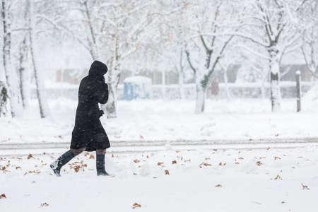 Vrouw, gekleed in alleen zwarte jas lopen tijdens zware sneeuwstorm op de besneeuwde stoep in de woonwijk Stockfoto