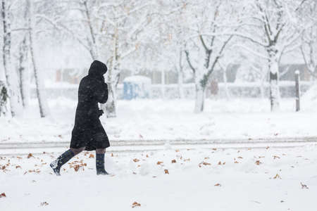 Woman dressed in black coat walking alone during heavy snowstorm on the snow covered pavement in the residential area