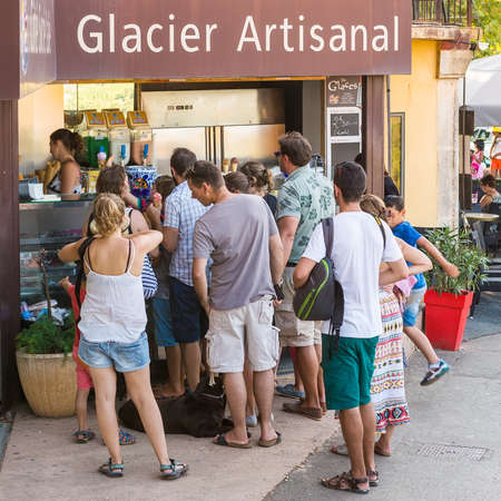 ROUSSILLON, FRANCE - AUGUST 11, 2015: Tourists ni front of the icrecream shop on the street. Roussillon  It is famous for large ochre deposits found in clay surrounding village.
