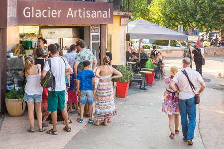 roussillon: ROUSSILLON, FRANCE - AUGUST 11, 2015: Tourists ni front of the icrecream shop on the street. Roussillon  It is famous for large ochre deposits found in clay surrounding village.