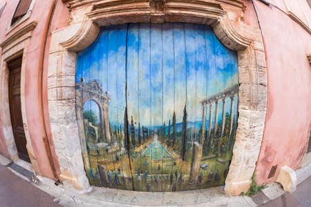old wooden door: ROUSSILLON, FRANCE - AUGUST 11, 2015: Old wooden door with painted picture of a garden with lake. Roussillon is famous for large ochre deposits found in clay surrounding village. Editorial