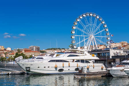 yacht: CANNES, FRANCE - AUGUST 17, 2015: Mega yachts docked at Cannes harbour, with city in the background. Cannes is one of the bigest French tourist cities.