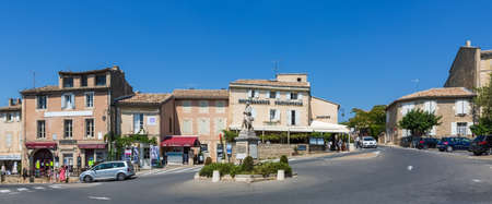gordes: GORDES, FRANCE - AUGUST 12, 2015: Main square with bars, restaurants and a roundabout in village of Gordes, situated on top of a hill in French region Provence.