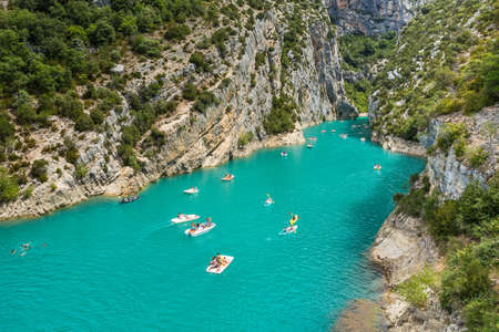 green river: GORGES DU VERDON, FRANCE - AUGUST 15, 2015: People rowing during recreation in Verdon Gorge canyon, on the mouth of Le Verdon river, near Aiguines. Canyon is about 25 kilometres long and up to 700 metres deep.