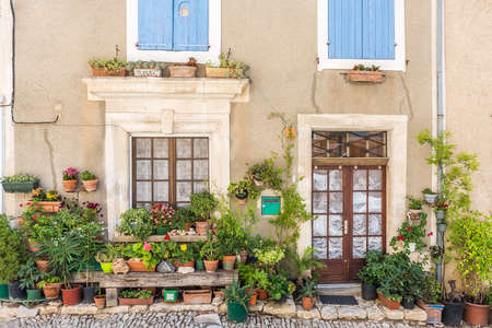 street life: Street with greenery in flower pots on the floor and the walls in Saint-Saturnin-les-Apt, France Stock Photo