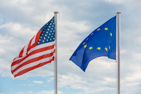 Flags of Un ited States of America and European Union hanging on poles, waving in the wind
