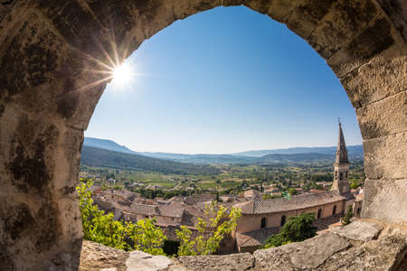 apt: Church in Saint-Saturnin-les-Apt, seen through the ruined fortress window above. City is situated at the dominant position on the Monts de Vaucluse facing south towards the Luberon. It has around 3000 inhabitants.