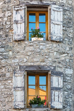 open windows: Open windows on an old house with walls made of rock, with flowers growing in flower pots