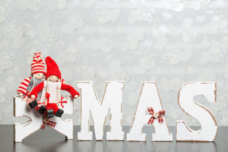 romatic: White wooden letters on brown wooden table forming word XMAS with ribbons and a couple represented by red figures sitting on letter X Stock Photo