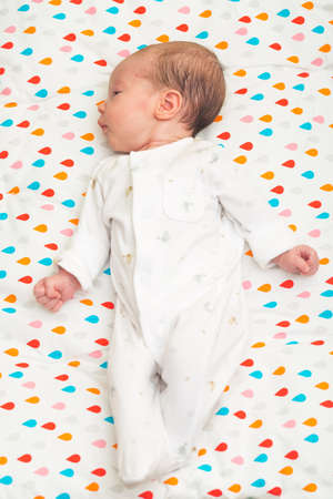 back of head: Newborn baby dressed in white sleeping on her back, head to the side Stock Photo