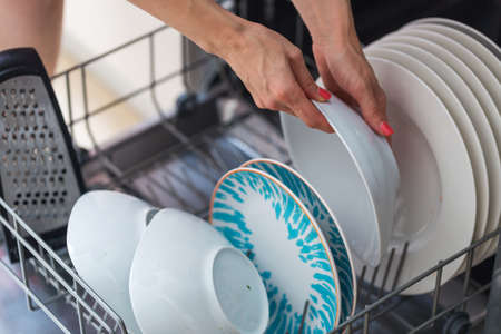 Womans hand putting a white plate into the dishwasher; a household chore Standard-Bild