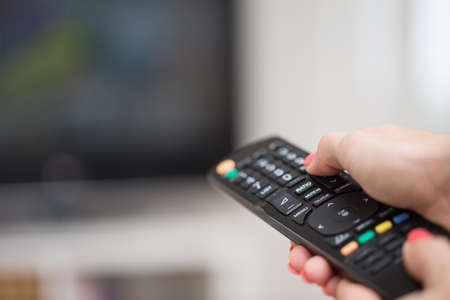 changing channels: Female hand holding a TV remote control pointed towards the LCD television screen in the background; changing channels Stock Photo